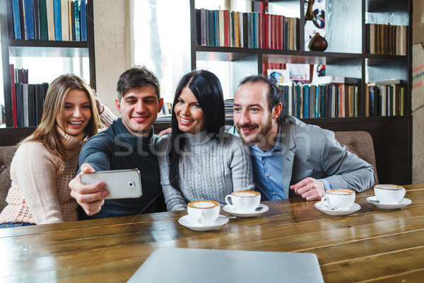 Group of friends with coffee and looking at smartphone Stock photo © chesterf