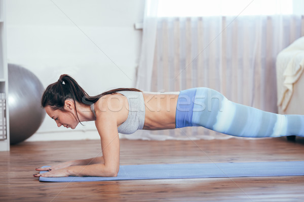 Slim fitness young woman doing plank exercise at home . Stock photo © chesterf