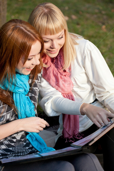 two laughing sisters with photo album in the park Stock photo © chesterf
