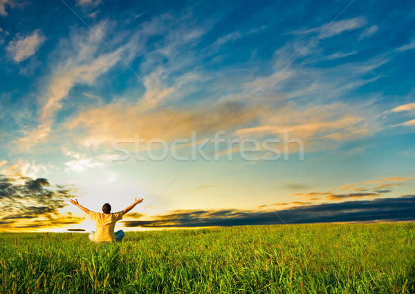 man sitting in the field under sunset Stock photo © chesterf