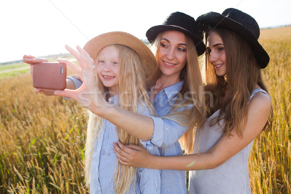 beautiful young mother and her daughters at the wheat field Stock photo © chesterf