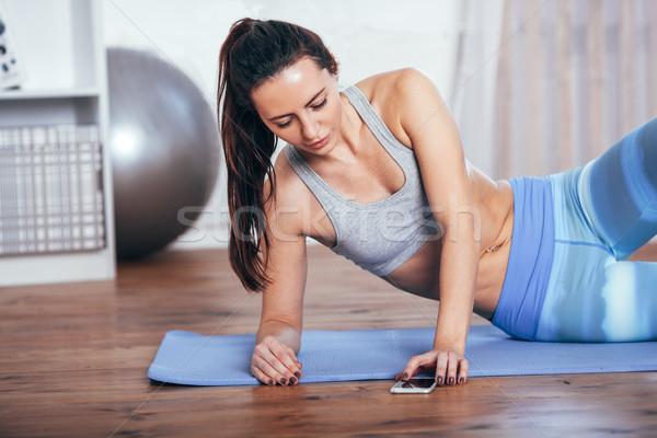 Szczupły fitness młoda kobieta wykonywania domu smartphone Zdjęcia stock © chesterf