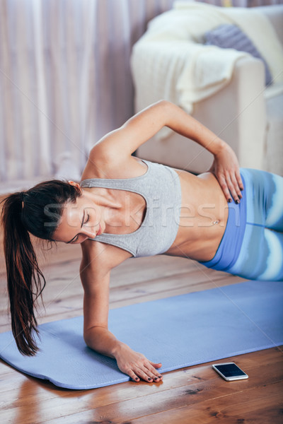 Slim fitness young woman doing side plank exercise at home with smartphone Stock photo © chesterf