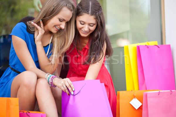 Stock photo: Two girls show each other the purchase