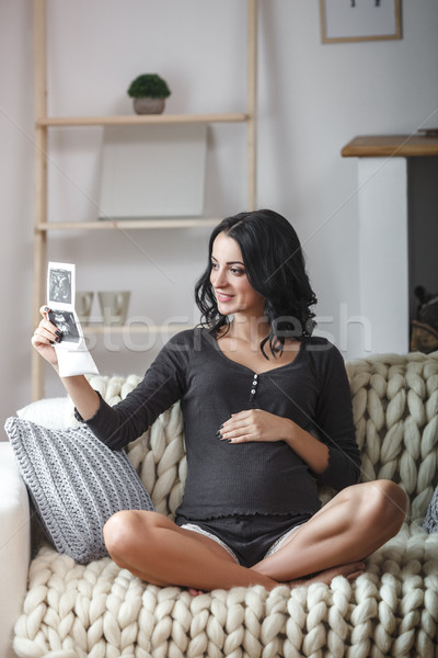 happy beautiful pregnant woman relaxing on sofa with echo in hands Stock photo © chesterf
