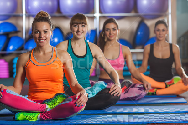 women sitting in lotus pose on mat at gym Stock photo © chesterf