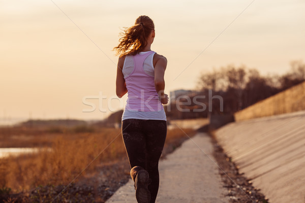 Female fitness woman training outside on a warm fall day Stock photo © chesterf