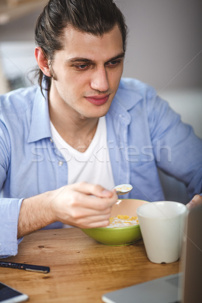 Jonge man eten cornflakes melk en naar Stockfoto © chesterf