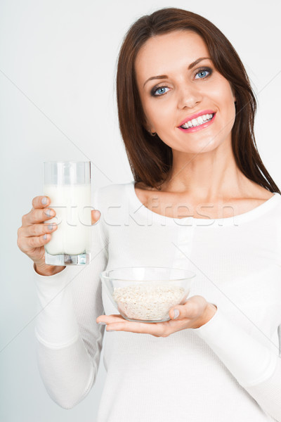 woman holding glass of mik and bowl with oatmeal Stock photo © chesterf