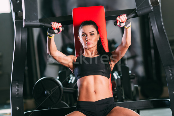 Stock photo: caucasian woman exercising on shoulder press machine