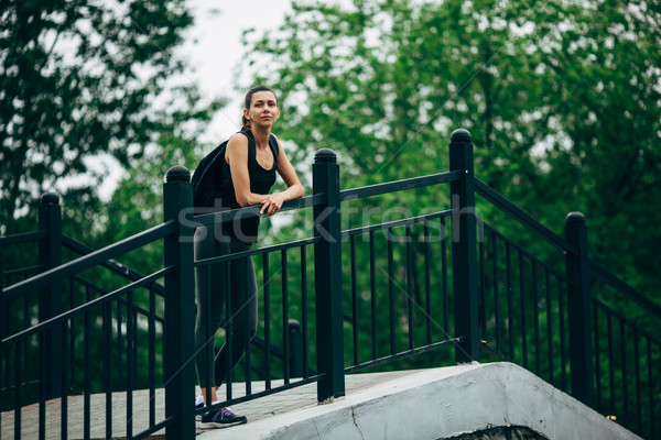 woman wearing sports wear standing on bridge Stock photo © chesterf