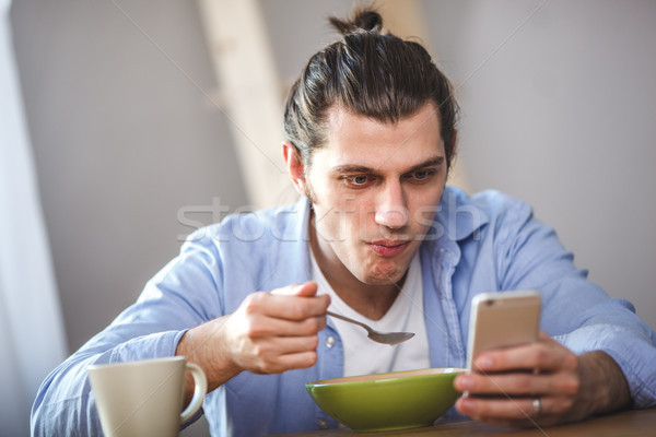 Young man eating corn flakes with milk and and looking to thesmartphone screen Stock photo © chesterf