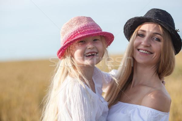 Gyönyörű fiatal anya lánygyermek búzamező átkarol Stock fotó © chesterf