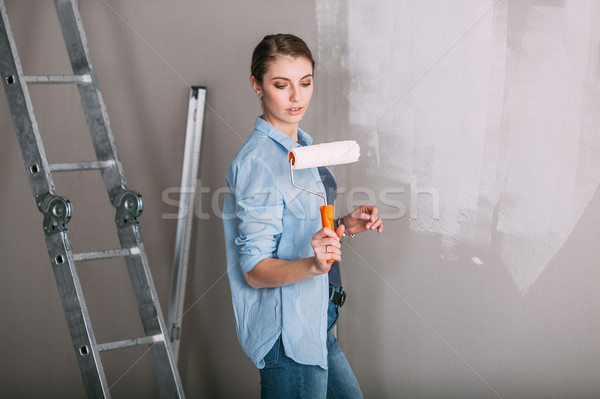 beautiful young woman looking at wall and holding roller Stock photo © chesterf