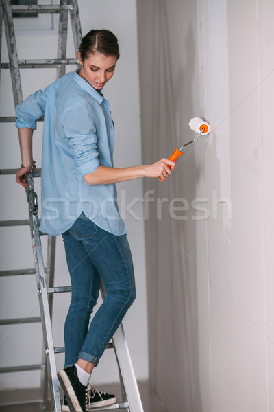 Woman stands on a ladder to paint her walls white Stock photo © chesterf