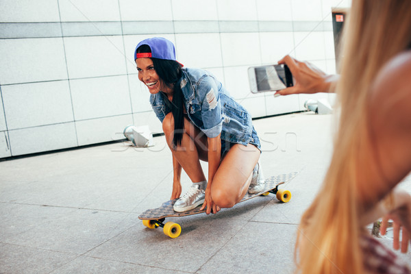 one woman shooting other on longboard Stock photo © chesterf