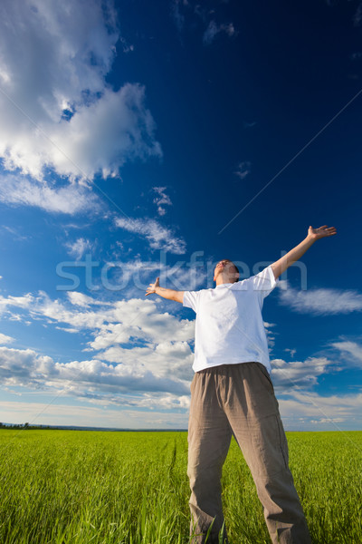 man on field rising up hands Stock photo © chesterf
