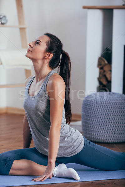 Stock photo: Young attractive smiling woman practicing yoga at home