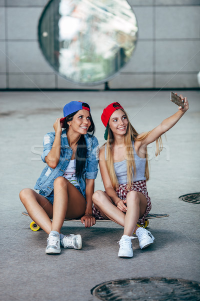 two young girls sitting on longboard Stock photo © chesterf
