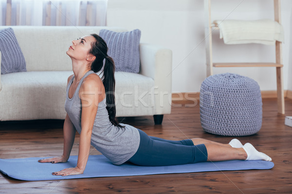 Stock photo: Full length side view portrait of beautiful young woman working out at home, doing yoga or pilates e