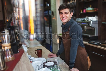 Male cashier smiling for young woman in cafe Stock photo © chesterf