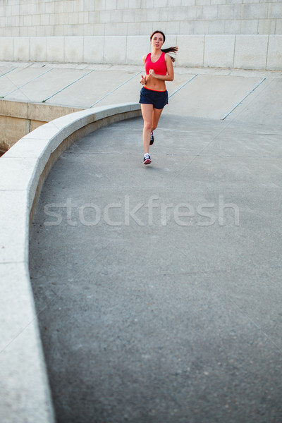 woman runnning along granite curved parapet Stock photo © chesterf