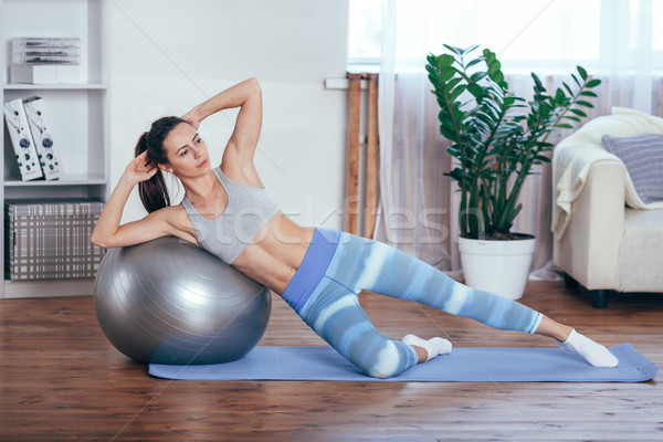 Young sportswoman doing exercises with ball on a mat at home Stock photo © chesterf