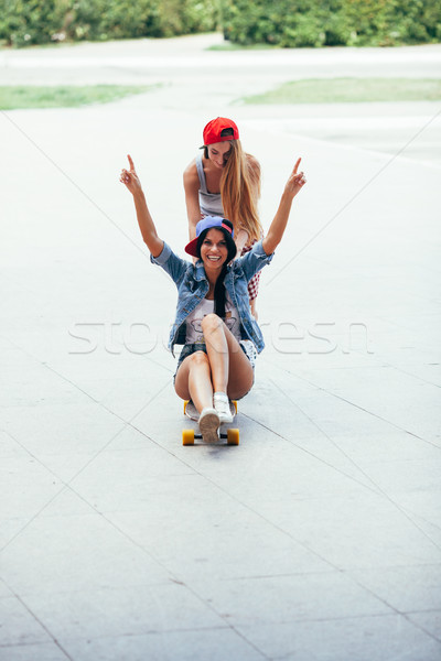 one woman riding other on longboard Stock photo © chesterf