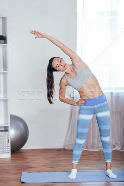 Beautiful young woman dressed in sportswear doing yoga indoors. Stock photo © chesterf