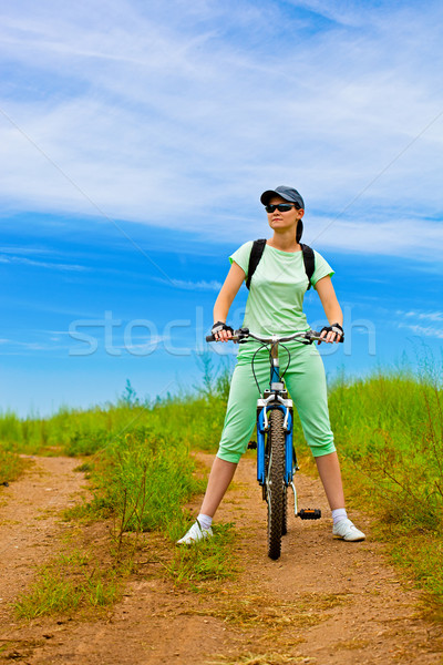 woman with bike on green field Stock photo © chesterf
