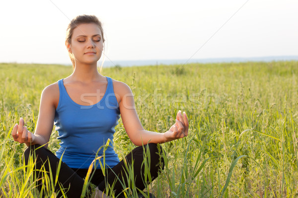 woman on filed in lotus pose Stock photo © chesterf