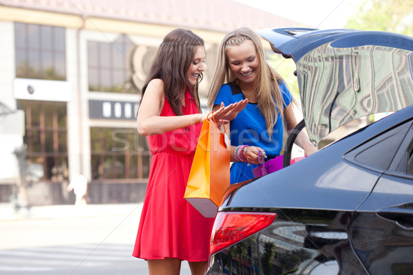 Stock photo: two girls are piling the bags in the car