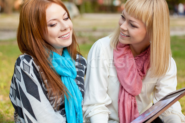 two beautiful sisters with photo album in the park Stock photo © chesterf