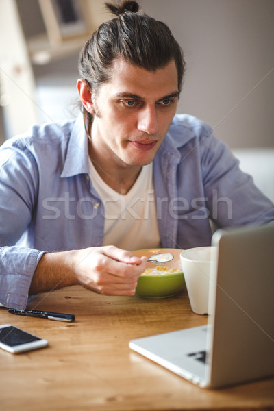 Fiatalember eszik gabonapehely tej és néz Stock fotó © chesterf