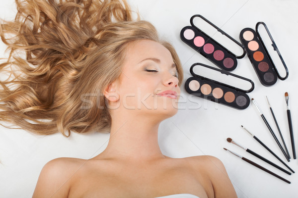 woman laying on floor with eyeshadows and brushes Stock photo © chesterf