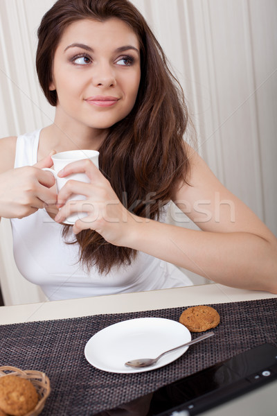 Happy woman enjoying tea and cookies Stock photo © chesterf