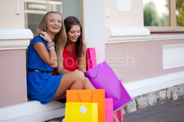 Two girls show each other the purchase Stock photo © chesterf