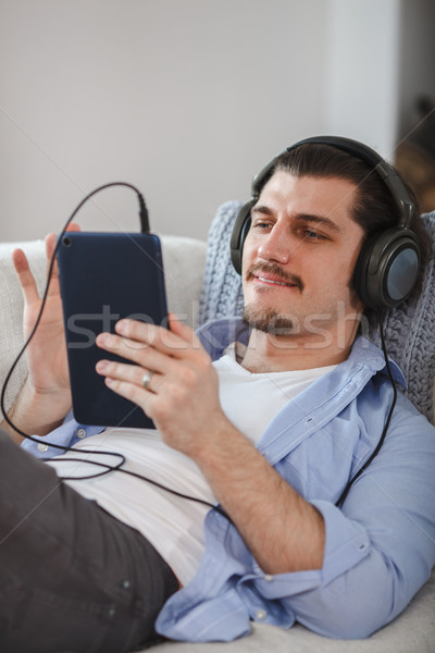 Jóképű fickó kanapé tabletta fejhallgató szakállas Stock fotó © chesterf