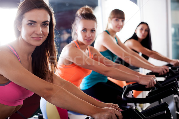 Group of four women in the gym cycling Stock photo © chesterf