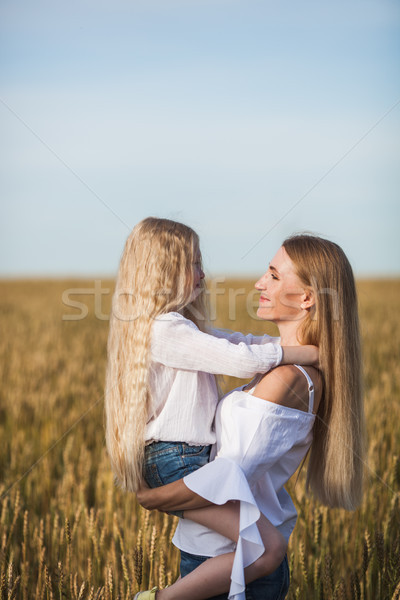 Stock photo: beautiful young mother and her daughter at the wheat field