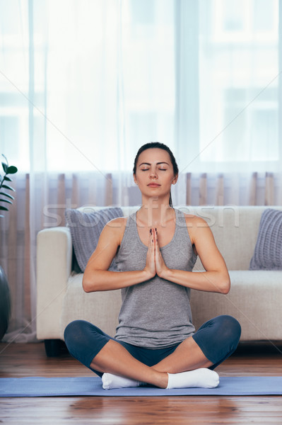 attractive young woman sitting on lotus position on floor with eyes closed. Stock photo © chesterf