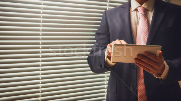 Entrepreneur working on digital tablet  Stock photo © choreograph