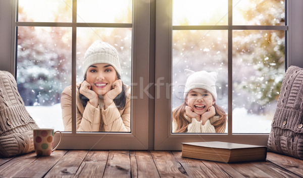 Child and mom looking in windows, standing outdoors Stock photo © choreograph