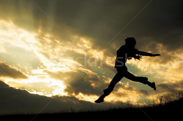 Springen Mädchen Sonnenuntergang Himmel Sonne Licht Stock foto © choreograph
