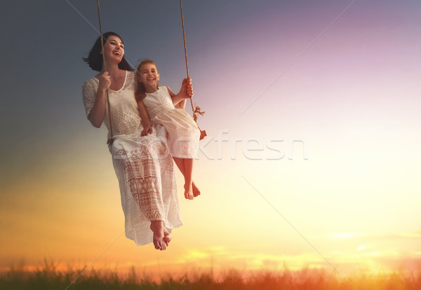Stock photo: mother and  daughter swinging on swings