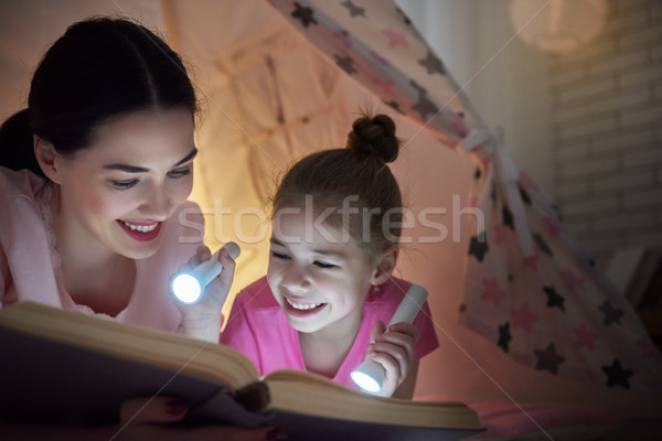 Mom and child are reading book Stock photo © choreograph