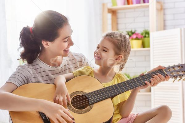 Foto d'archivio: Madre · figlia · giocare · chitarra · famiglia · felice · insieme