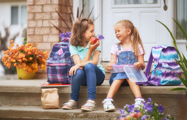 Girls with backpacks are eating fruit Stock photo © choreograph