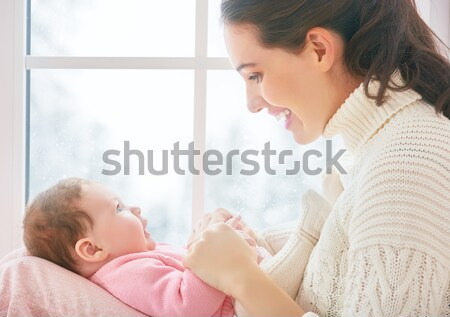 Mother and baby hugging near window Stock photo © choreograph