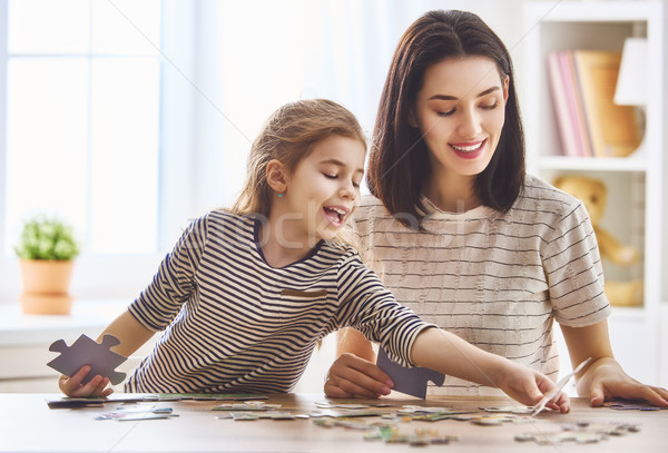 Mother and daughter do puzzles Stock photo © choreograph